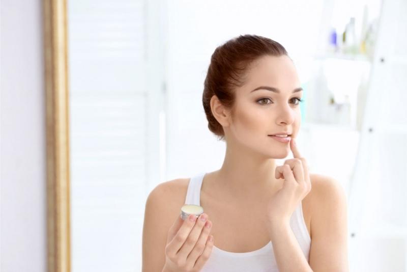 viso bella donna applica balsamo labbra specchio