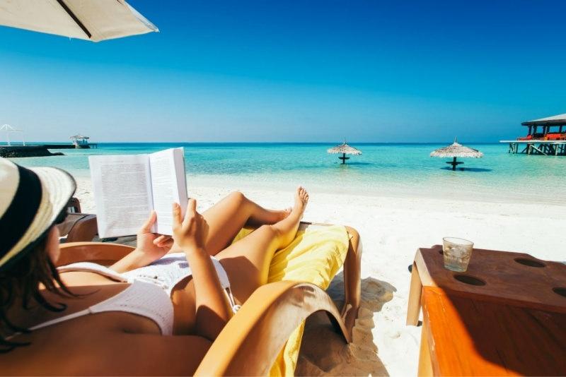 estate donna legge libro sotto ombrellone mare