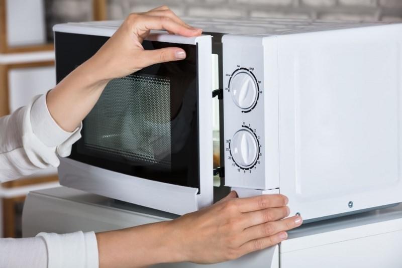 mani donna chiudono sportello forno a microonde