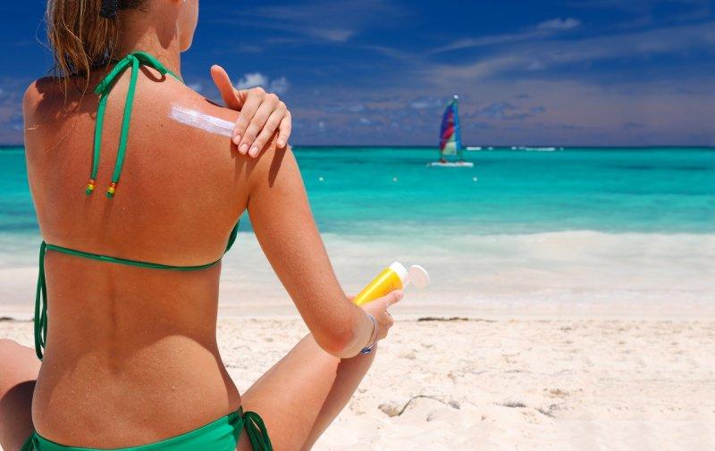 donna in bikini verde spalle arrossate si spalma protezione solare sulla spalla pelle estate mare spiaggia