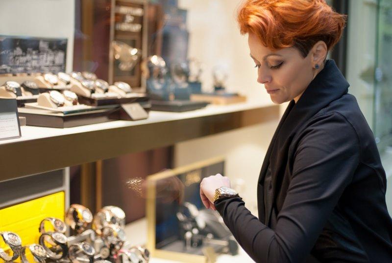 donna capellirossi corti guarda orologio davanti vetrina negozio orologi
