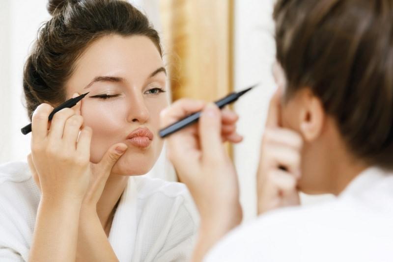 errore applicazione eyeliner bella donna allo specchio