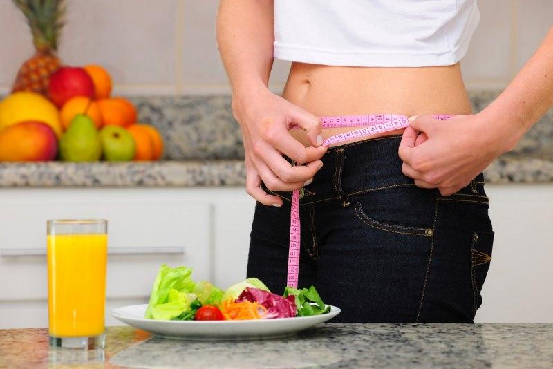 donna misura girovita con metro sarta piatto verdure insalata bicchiere arancia frutta