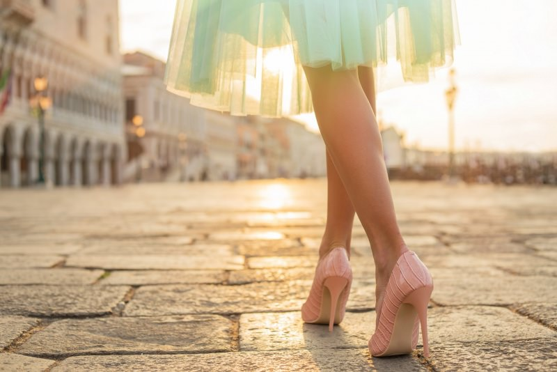 donna elegante abito cerimonia tulle scarpe décolleté rosa cammina tramonto
