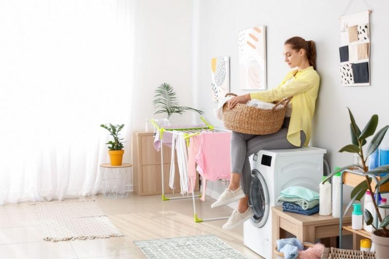 giovane donna seduta lavatrice aspetta bucato lavanderia