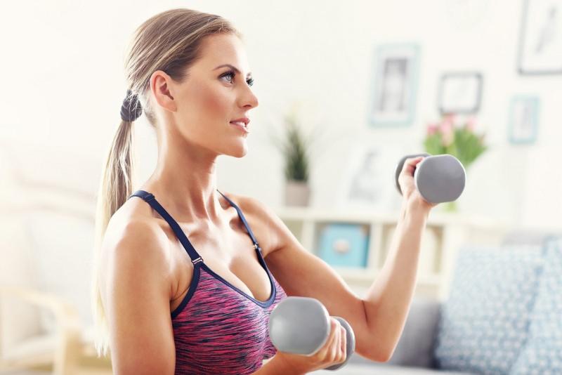 fitness donna esercizi braccia petto con manubri a casa