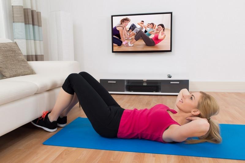 donna fa esercizi fisici addominali piedi sotto divano soggiorno davanti la televisione
