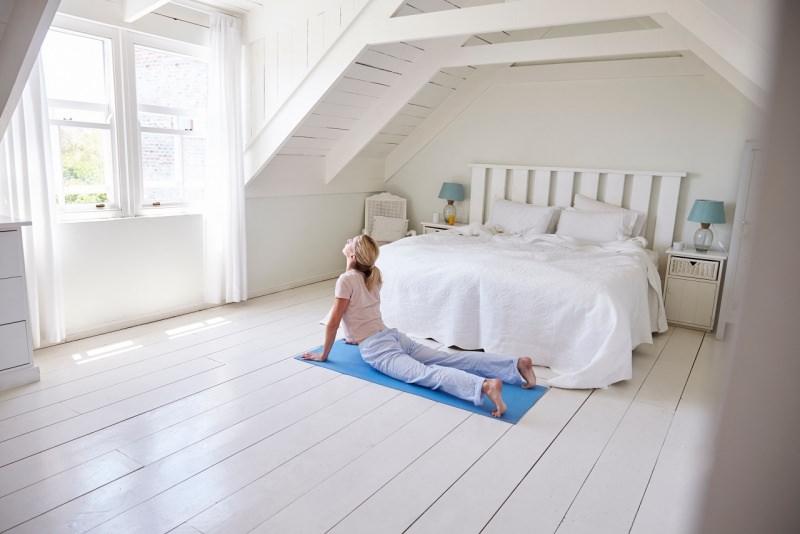 donna fa stretching su tappeto davanti letto
