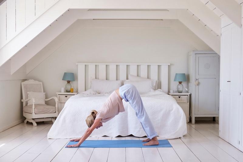donna fa attività fisica stretching davanti al letto su tappeto