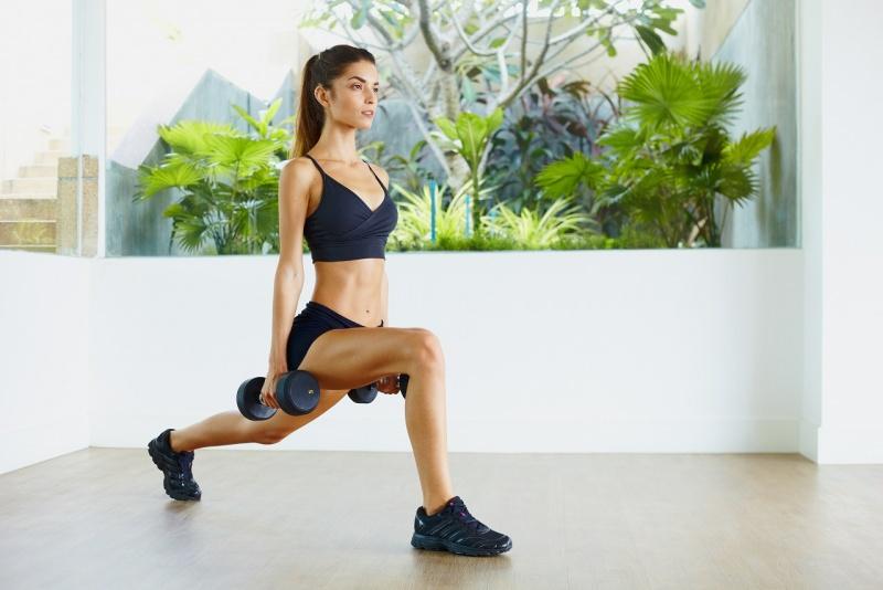 giovane donna atletica fa gli affondi con pesi in casa piante