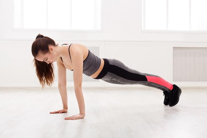 esercizi fisici donna fa flessioni piegamenti sulle braccia push upsin casa