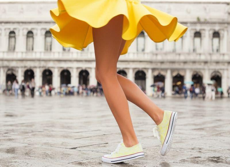donna felice gonna giallo e sneakers gialle gambe stile