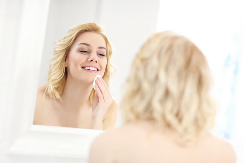 viso donna bionda sorridente mentre si strucca allo specchio con dischetto di cotone