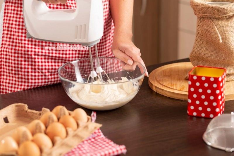 donna grembiule qudretti rosso bianco preparazione torta sbattitore uova ciotola vetro