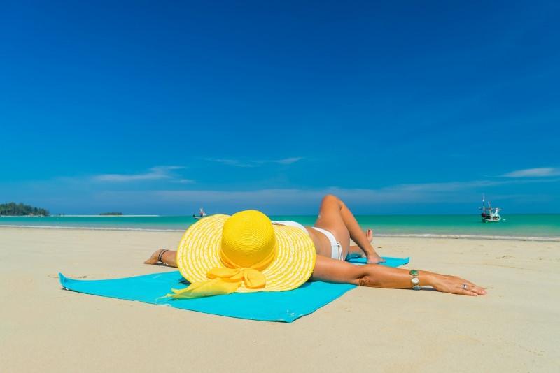 donna sdraiata sulla spiaggia cappello di paglia mare sabbia estate abbronzatura
