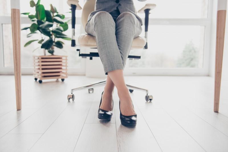 donna seduta in ufficio dettaglio gambe incrociate piedi scarpe con tacco pianta verde