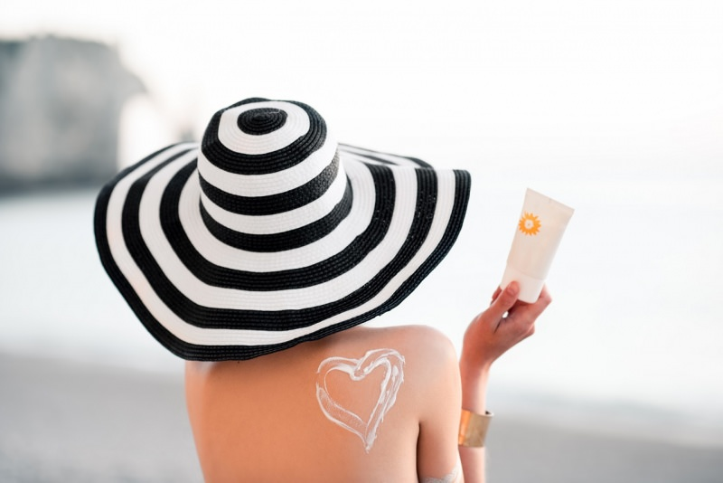 donna di spalle cappello a faldalarga bianco nero cuore crema lozione protezione solare