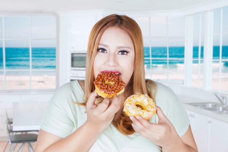 donna golosa sovrappeso mangia due ciambelle dolci