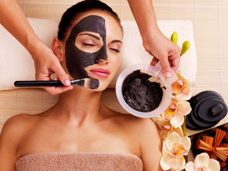 maschera viso al cioccolato su viso donna in relax applicato con pennello fiori orchidea