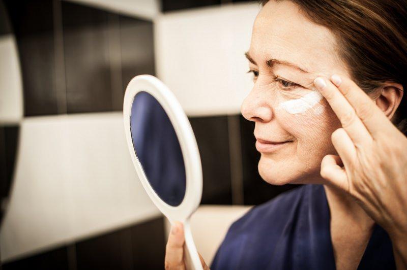 donna matura mette crema rughe davanti lo specchio