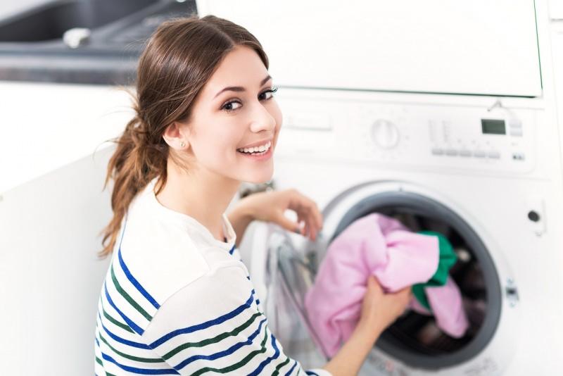 bella donna sorridente mette bucato nella lavatrice