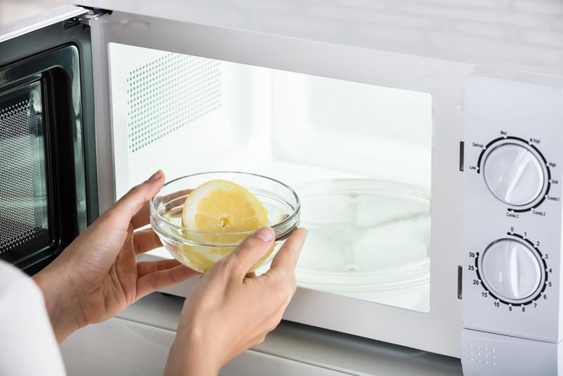 pulizia forno a microonde mani donna mettono ciotola vetro con succo e fetta limone