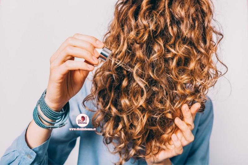 donna definisce styling capelli ricci con olio bracciale