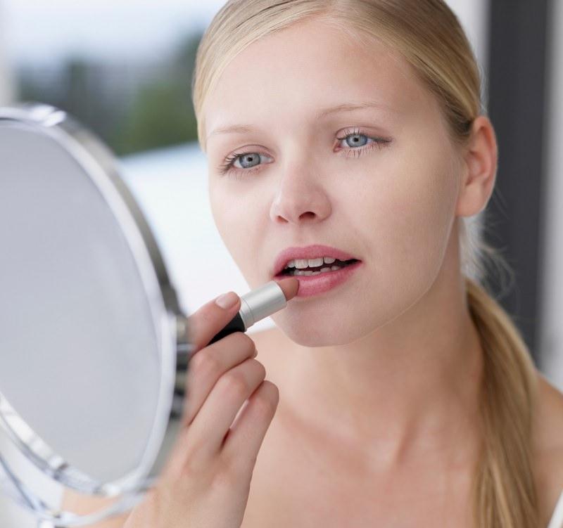 bella donna capelli biondi si mette il rossetto guardandosi allo specchio