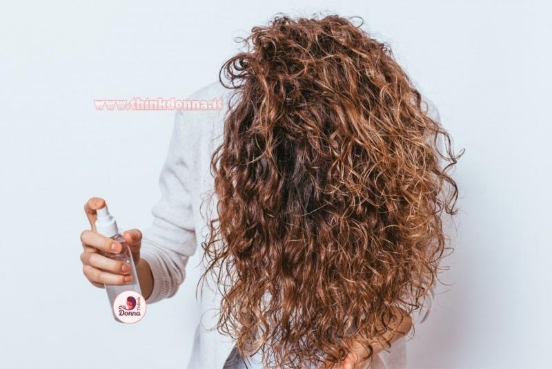 donna mette spray districante su capelli ricci