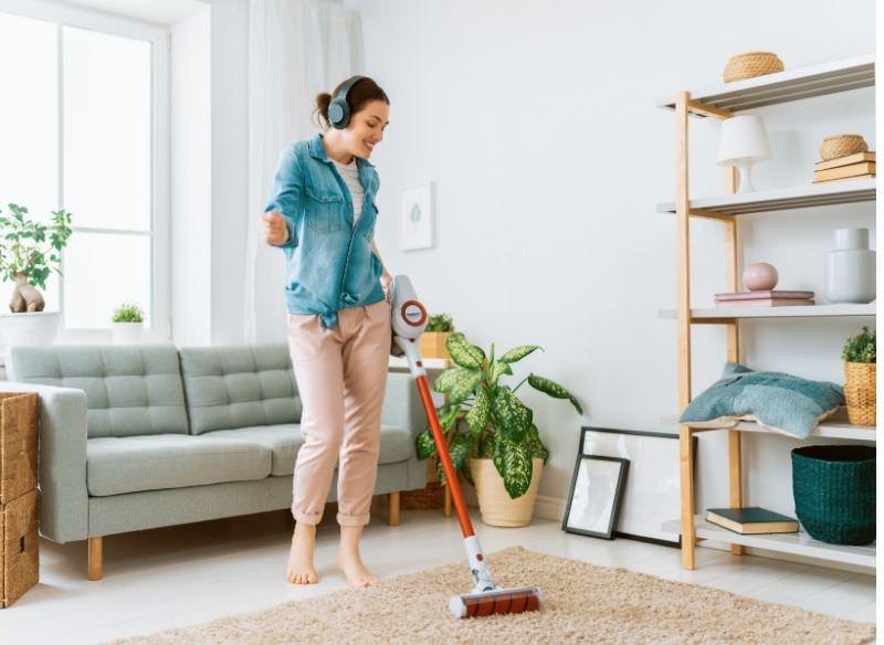 donna snella passa aspirapolvere mentre ascolta musica cuffie wireless pulizie casa soggiorno divano tappeto