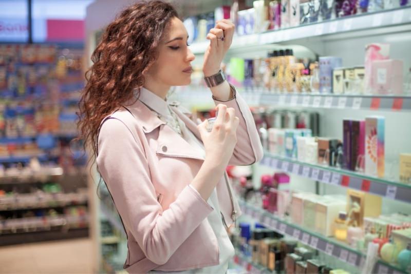 giovane donna capelli ricci prova profumo negozio