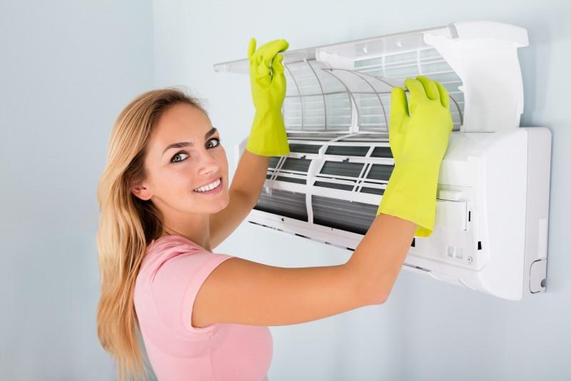 controllo pulizia condizionatore d'aria donna sorridente capelli lunghi biondi guanti di gomma gialli