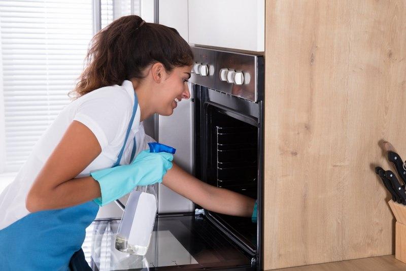 donna pulisce forno in cucina pulizie di primavera
