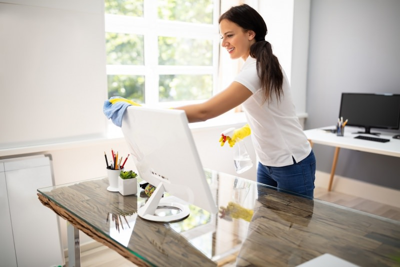 donna pulisce monitor lcd scrivania pulizie