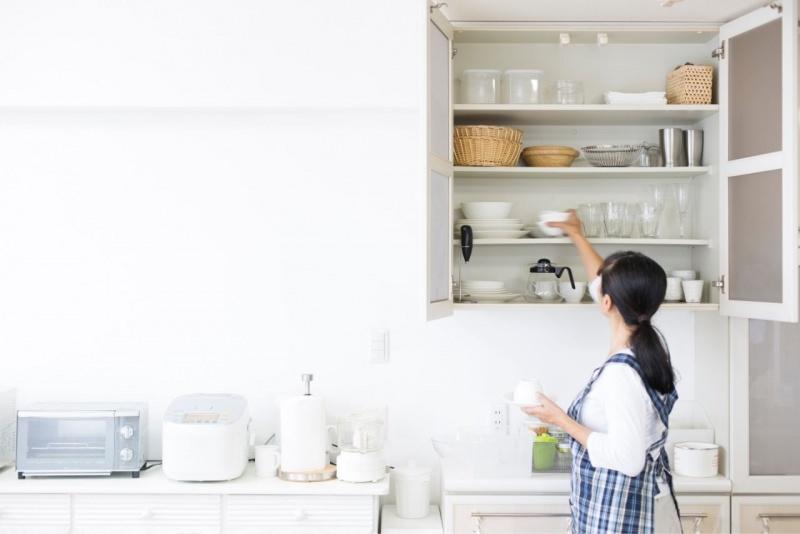 donna ripone stoviglie mobiel cucina sistemazione ordine pulizia