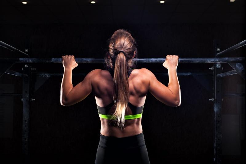 donna fisico atletico fa esercizi sbarra pull up