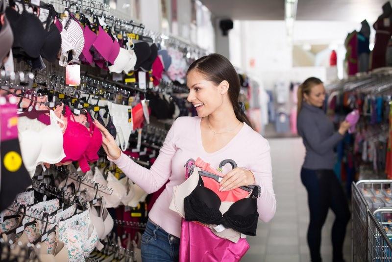donna sorridente sceglie biancheria intima reggiseno negozio