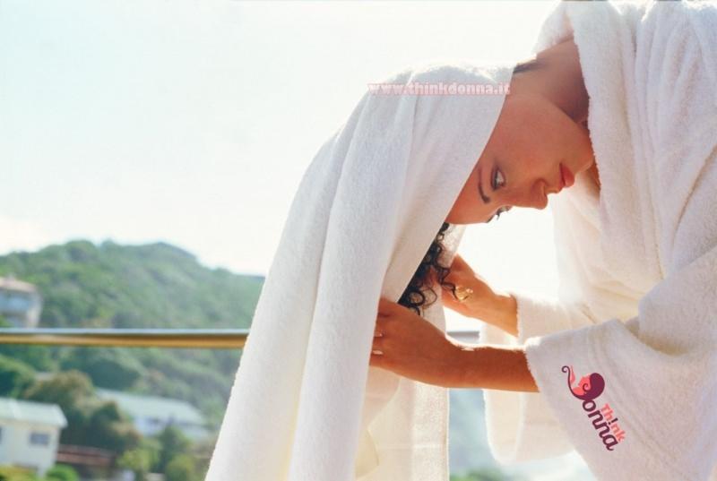 donna asciuga i capelli con telo spugna accappatoio bianco