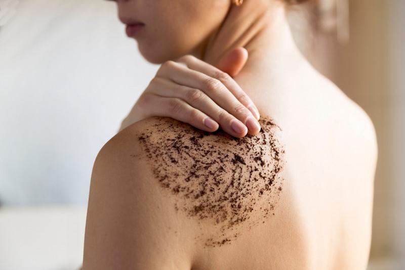 donna massaggia scrub caffè su pelle spalle