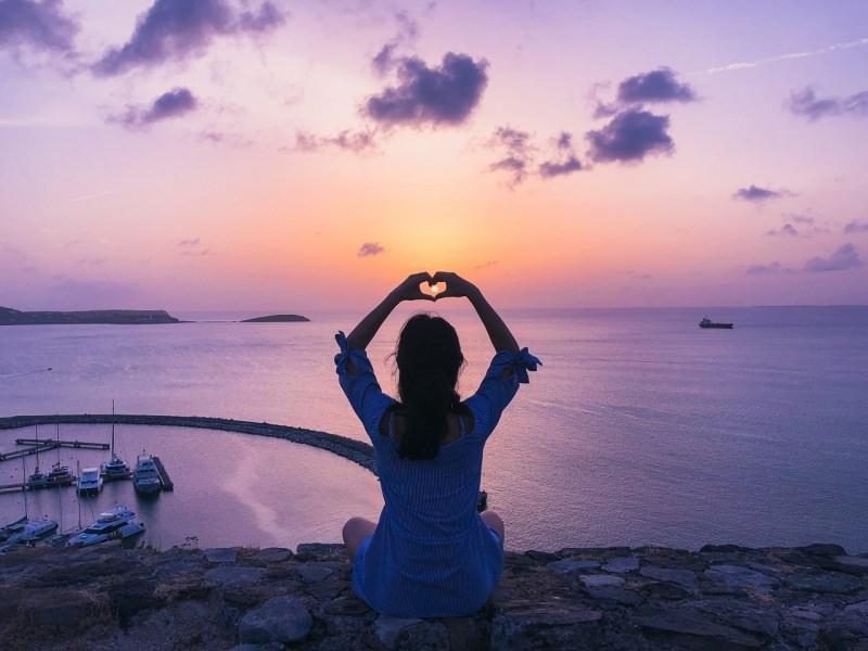 donna seduta cuore con le mani sole tramonto mare pensiero per chi non c'è più