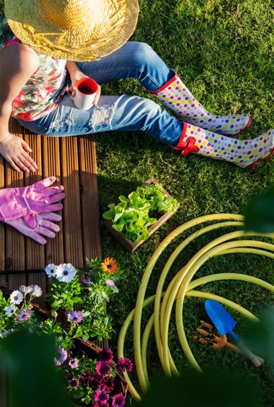 giovane donna jeans cappello di paglia sotto il sole relax riposo giardinaggio tubo acqua tazzina caffè stivali giardino
