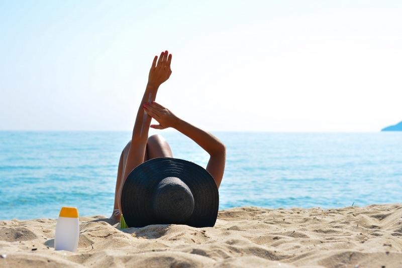 donna sdraiata sulla sabbia mare sole si spalma protezione solare cappello estate