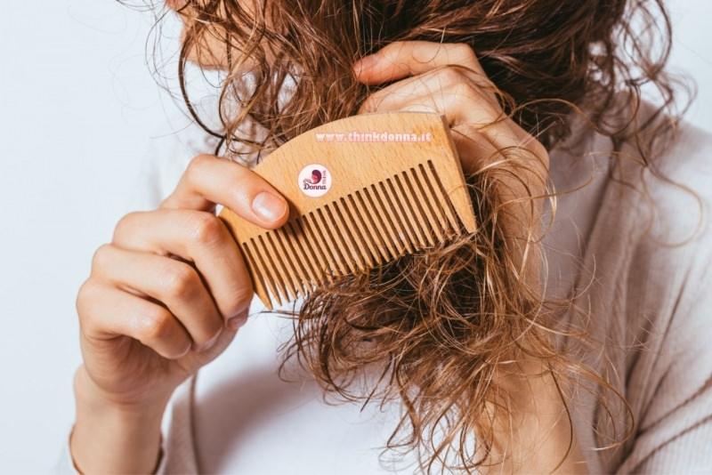 donna pettina i suoi capelli ricci con un pettine di legno