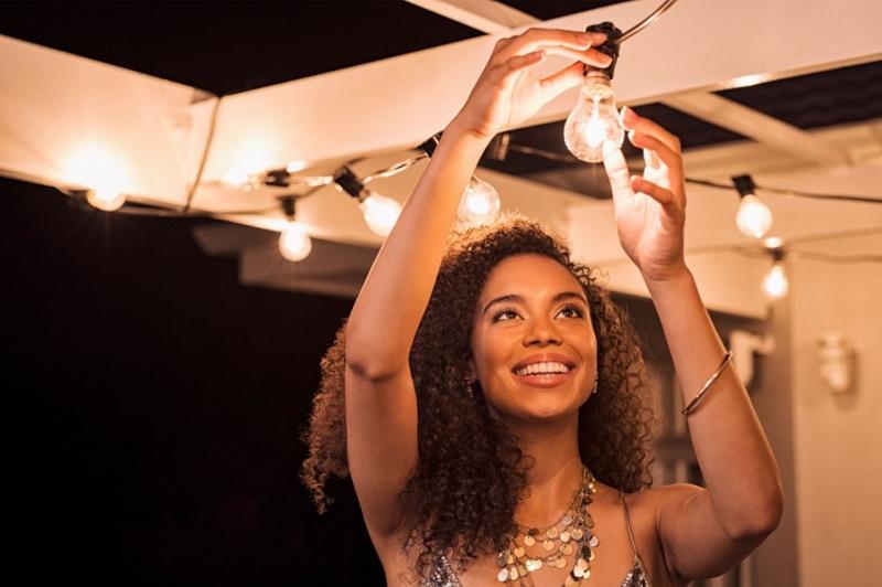 giovane donna sorridente sistema lampadina illuminazione terrazza aperto