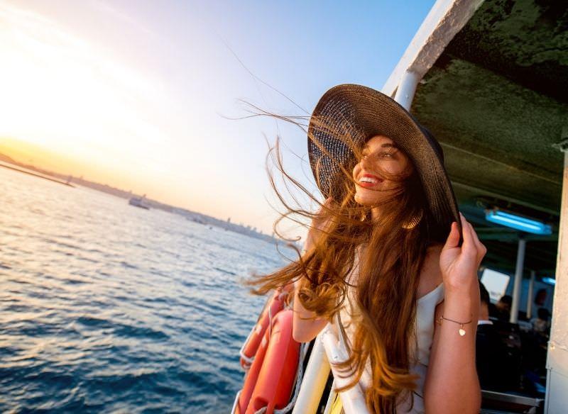 bellissima donna sorridente guarda mare dal traghetto capelli lunghi vento cappello sole sorriso