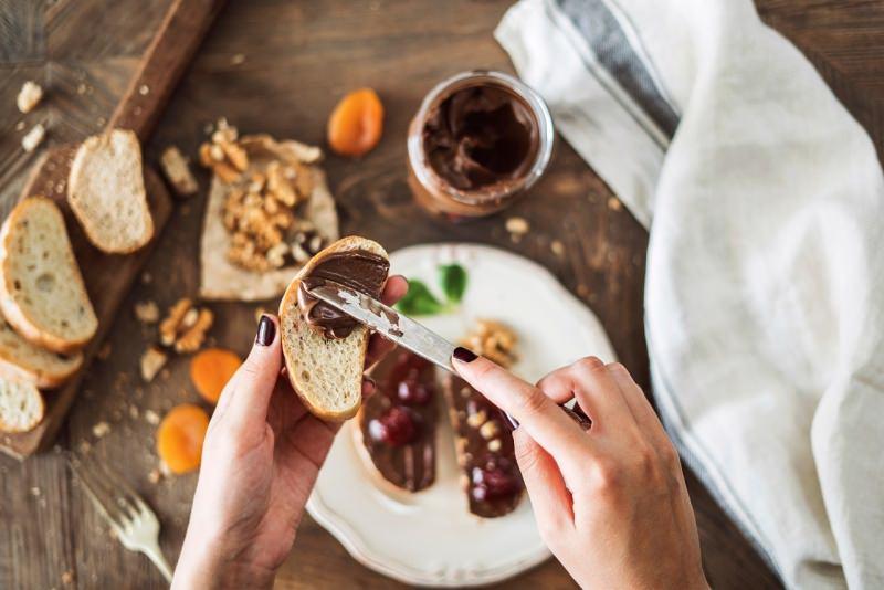 mani di donna spalma crema cioccolato nocciole fetta di pane tagliere albicocche
