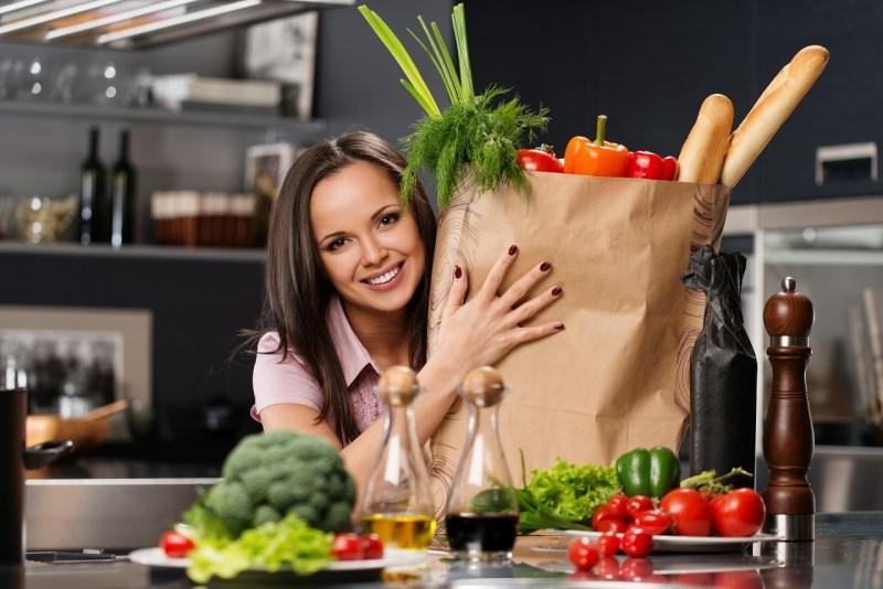donna sorridente sacco spesa in cucina pane frutta e verdure