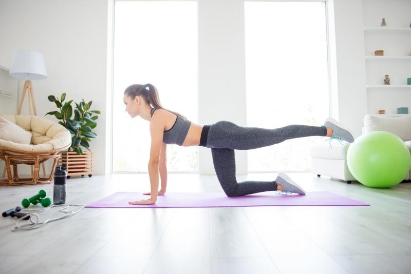 donna fa esercizio fisico glutei sodi donkey kick in casa