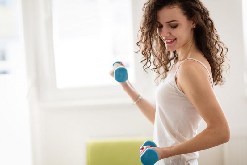bella donna fitness esercizi con manubri sorrso