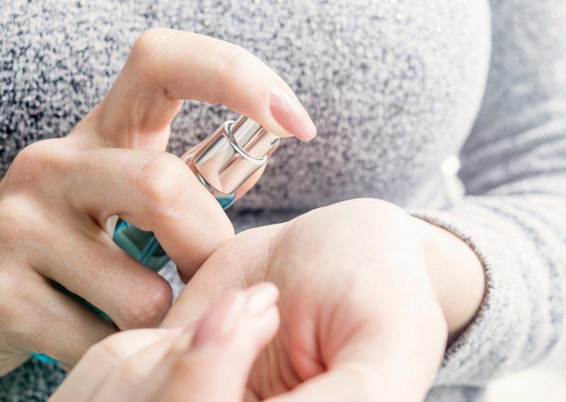 mani di sonna unghie lunghe smalto rosa spruzza profumo sul polso